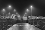 A b&w image of the Gatun locks in the Panama Canal at nighttime.