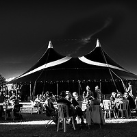 People sitting in summer sunshine beside large tent