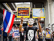 "14 JULY 2013 - BANGKOK, THAILAND:  A man carries signs comparing Thai Prime Minister Yingluck Shinawatra to a crab. The signs are a play on words because Yingluck's nickname is ""Pu"" and pu is also the Thai word for crab. About 150 members of the so called ""White Mask"" movement marched through the central shopping district of Bangkok Sunday to call for the resignation of Yingluck Shinawatra, the Prime Minister of Thailand. The White Mask protesters are strong supporters of the Thai monarchy. They claim that Yingluck is acting as a puppet for her brother, former Prime Minister Thaksin Shinawatra, who was deposed by a military coup in 2006 and now lives in exile in Dubai.       PHOTO BY JACK KURTZ"