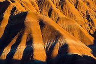 Sunset light on layered sediment rock on eroded hills along the Cockscomb, Grand Staircase Escalante National Monument, Utah