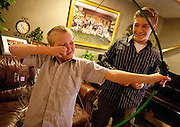 Joseph Sebaske, right, shows his younger brother, Michael some of the finer points of his new bow and arrow donated by LDS Hospital employees from the Blood and Marrow Transplant division at the Sebaske residence in Sandy, Monday, Dec. 17, 2012.
