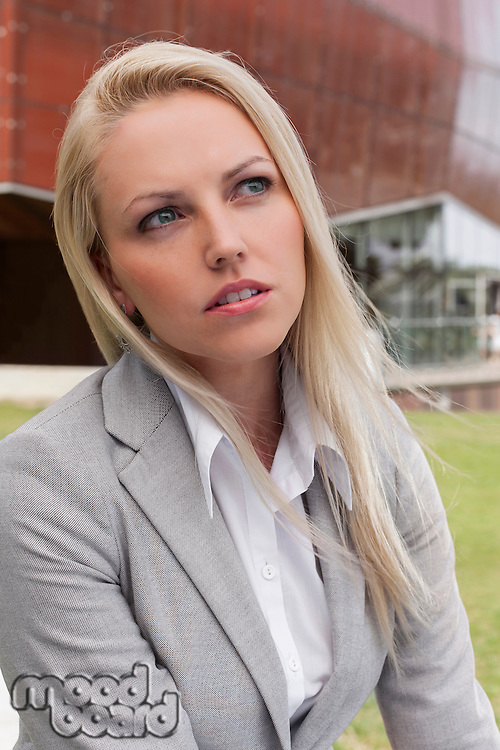 Close-up of thoughtful young businesswoman looking away against office building