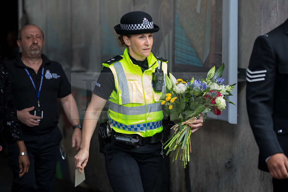 © Licensed to London News Pictures. 03/06/2018. London, UK. A policewoman carries flowers to lay on London Bridge to mark one year since the London Bridge and Borough Market terror attacks. A series of events have taken place throughout the day, including a service of commemoration at Southwark Cathedral, the planting of an olive tree in the Cathedral grounds, a minute's silence at 4:30pm and the laying of flowers.  Photo credit : Tom Nicholson/LNP