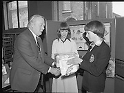 """1980-03-07.7th March 1980.07/03/1980.03-07-80..Photographed at Maguire & Paterson, Dublin..Basil Loves it:..Alan Buttanshaw, Managing Director of Maguire & Paterson shakes the hand of a £15 prize winner, Basil Love (16), """"Joppa Lodge"""". Rosses Point, Sligo as Ruth Buchanan, presenter of RTE's Poparama views proceedings."""