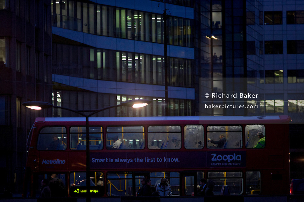 Commuters on both decks of a London bus, stopped on London Bridge, in the City of London.