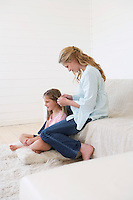 Mother sitting on couch plaiting daughter's hair