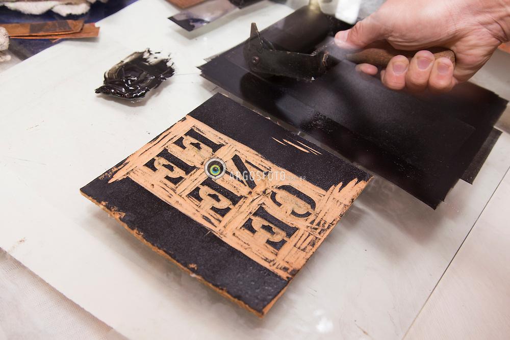 Xilogravura, e uma tecnica de gravura na qual se utiliza madeira como matriz e possibilita a reproducao da imagem gravada sobre papel ou outro suporte adequado. Processo parecido com um carimbo.Se entalha na madeira a figura ou forma (matriz) que se pretende imprimir. Apos este procedimento, usa-se um rolo de borracha embebida em tinta, tocando as partes elevadas do entalhe. O final do processo e a impressao em alto relevo em papel ou pano especial, que fica impregnado com a tinta, revelando a figura. /Woodcut or xylography, is a relief printing artistic technique in printmaking in which an image is carved into the surface of a block of wood, with the printing parts remaining level with the surface while the non-printing parts are removed, typically with gouges. The areas to show 'white' are cut away with a knife or chisel, leaving the characters or image to show in 'black' at the original surface level. Ano 2015.Foto Adri Fleden/Argosfoto