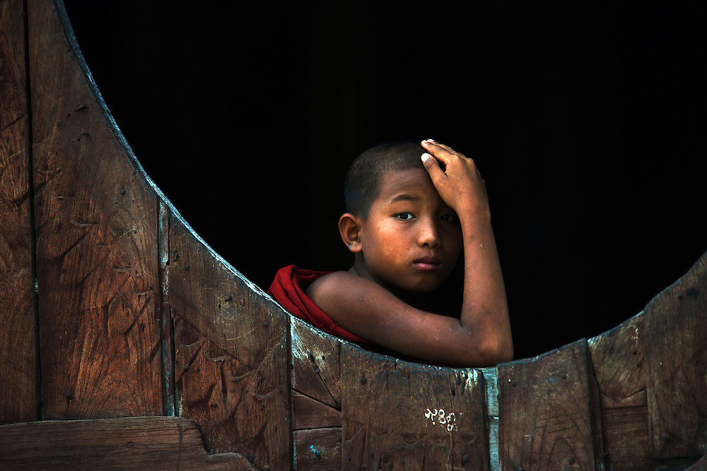 A young novice monk peers from one of the unique oval windows that characterize Shwe Yaunghwe Kyaung, teak wood monastery, Nyaungshwe.
