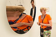 A woman and her distorted reflection in a polished stainless steel mirror by Aneesh Kapoor in the Lisson Gallery.