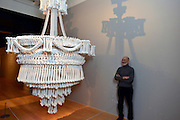 "© Licensed to London News Pictures. 14/11/2012. London, UK  Collector Richard Harris stands with ""In the Eyes of Others"" a huge chandelier made of 3000 plaster cast bones by British artist Jodie Carey. Press preview of ""Death: A Self -Portrait. The Richard harris Collection"" at The Welcome Collection today 14th November 2012. The exhibition showcases 300 works from a unique collection devote to the iconography of death and mankind's attitude towards it. Photo credit : Stephen Simpson/LNP"