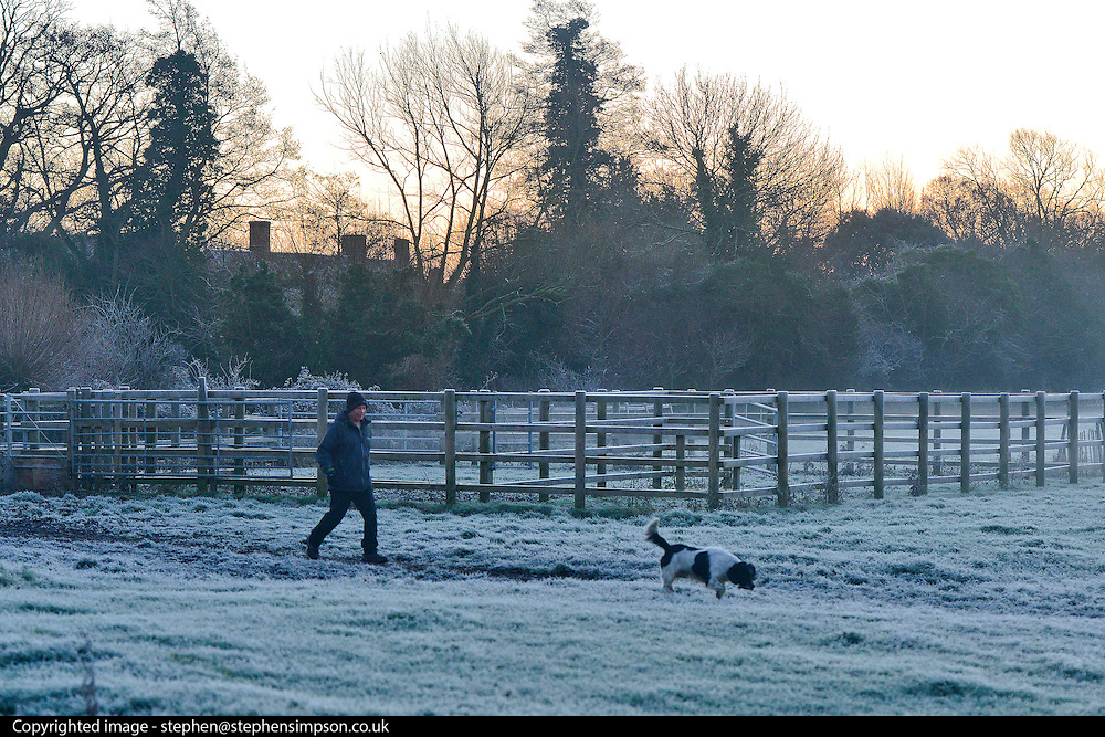 © Licensed to London News Pictures. 29/12/2013. East Bergholt, UK A man walks his dog at Flatford Mill. Early morning frost and mist on the River Stour at Deadham Vale this morning 29th December 2013. Photo credit : Stephen Simpson/LNP