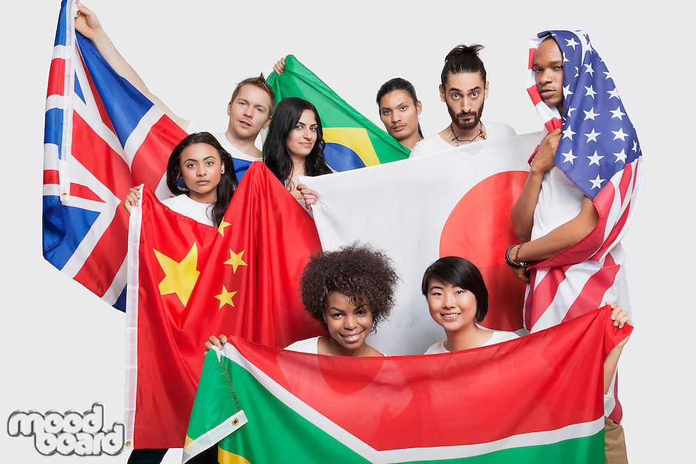 Group of multi-ethnic friends posing with various national flags against white background
