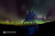 Aurora borealis over tipi display on Blackfeet Tribal Land near St Mary, Montana, USA