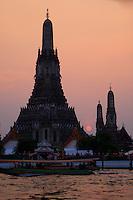 The sun sets behind Wat Arun on the banks of the Chao Praya River, Bangkok, Thailand