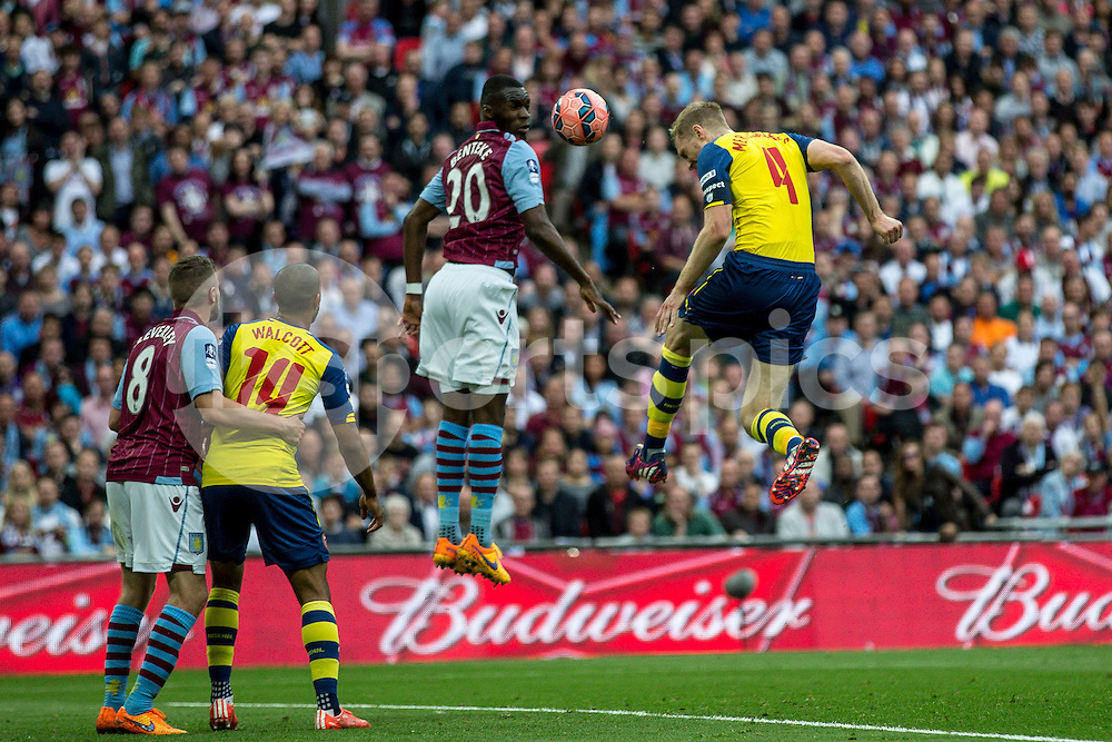 Per Mertesacker of Arsenal heads home the third goal during the The FA Cup Final match between Arsenal and Aston Villa at Wembley Stadium, London, England on 30 May 2015. Photo by Liam McAvoy.