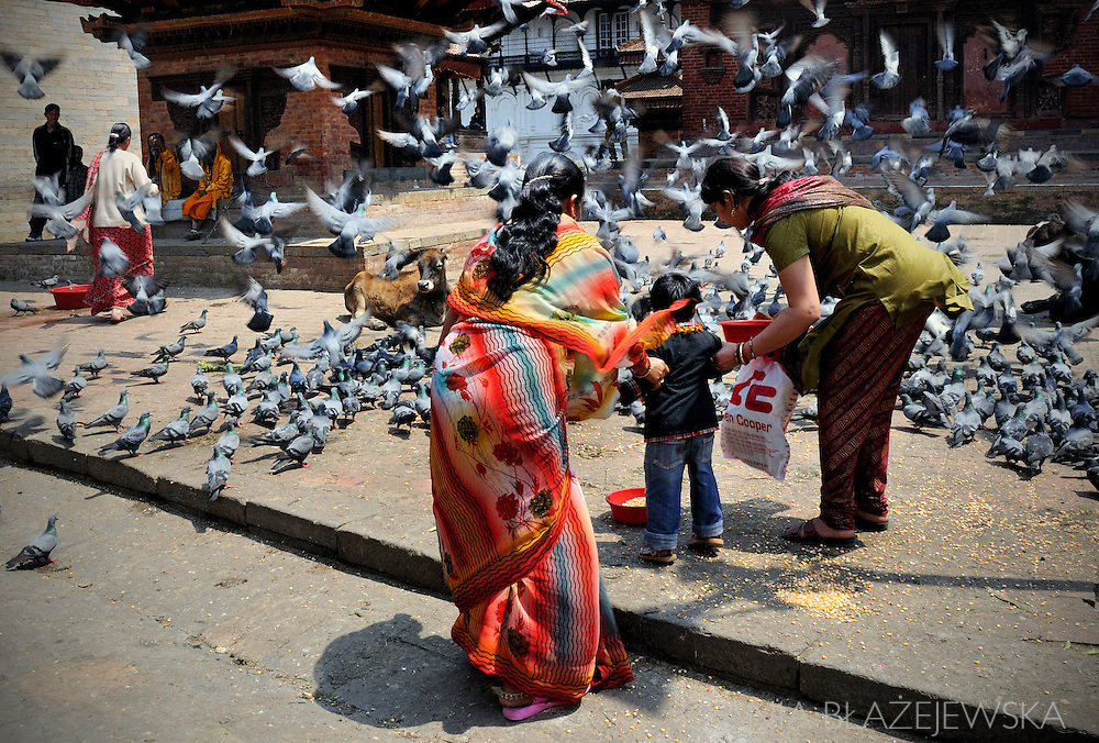 Nepal, Kathmandu. Women and a child feeding pigeons on Durbar Square.