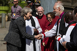 © Licensed to London News Pictures . 22/05/2018 . Manchester , UK . Prime Minister THERESA MAY is greeted by dignitaries , including Bishop DAVID WALKER (shaking hands) JOHN SENTAMU , SIR RICHARD LEESE and ANDY BURNHAM , wait to receive guests at Manchester Cathedral ahead of a Service of Remembrance on the first anniversary of the Manchester Arena bombing . On the evening of 22nd May 2017 , Salman Abedi murdered 22 people and seriously injured dozens more , when he exploded a bomb in the  foyer of the Manchester Arena as concert-goers were leaving an Ariana Grande gig . Photo credit : Joel Goodman/LNP