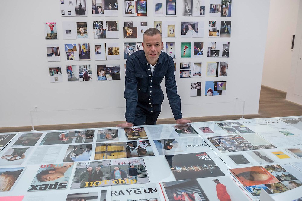 Tillman with Book covers, magazine spreads etc in room 9 - Wolfgang Tillmans: 2017. Tate Modern's new exhibition. Highlights include: large scale photographic works printed especially for this exhibition, including the four-meter tall Weed 2014 and dramatic seascapes such as The State We're In, A 2015;   New 'text and table' sculptures including Time Mirrored 3 2017, on display to the public for the first time; and slide projection Book for Architects 2014. The show is at Tate Modern from 15 February to 11 June 2017.