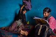 Poonam, 13, (right) is reviewing her homework and her older sister Jyoti, 14, is reaching her schoolbag for a pen, while sitting on the floor of their newly built home in Oriya Basti, one of the water-contaminated colonies in Bhopal, central India, near the abandoned Union Carbide (now DOW Chemical) industrial complex, site of the infamous '1984 Gas Disaster'.