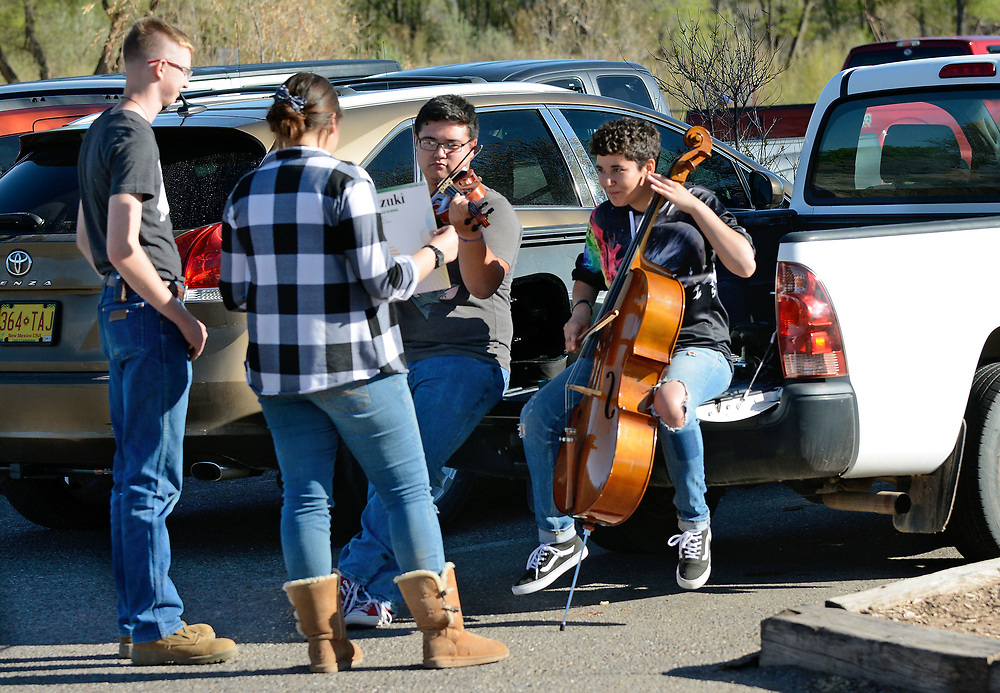 jt040517k/a sec/jim thompson/  RaeJean Lucero holds sheet music as Edwin Armijo plays violin and  her sister Elizabeth Lucero plays her cello with Travis Brown looking on in the parking area at the Alameda Open Space Parking area.   April 05, 2017. (Jim Thompson/Albuquerque Journal)