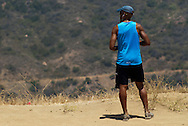 Young man at rest during his footing on a trail on the south face of Mt. Hollywood. Los Angeles, California.