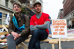 Two protesters await the start of yet more direct action as hundreds of environmental protesters from Extinction Rebellion occupy Marble Arch, camping in the square and even on the streets, blocking access to traffic on Park Lane and Oxford Street in London's usually traffic-heavy west end. . London, April 16 2019.