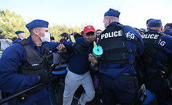 © London News Pictures. Hungarian police try to contain migrants as they broke out from the camp and joined the motorway and started walking towards Budapest close to the Hungarian and Serbian border town of Roszke, Hungary, September 7 2015. The UN's humanitarian agencies are on the verge of bankruptcy and unable to meet the basic needs of millions of people because of the size of the refugee crisis in the Middle East, Africa and Europe, senior figures within the UN have told the media.   Picture by Paul Hackett /LNP