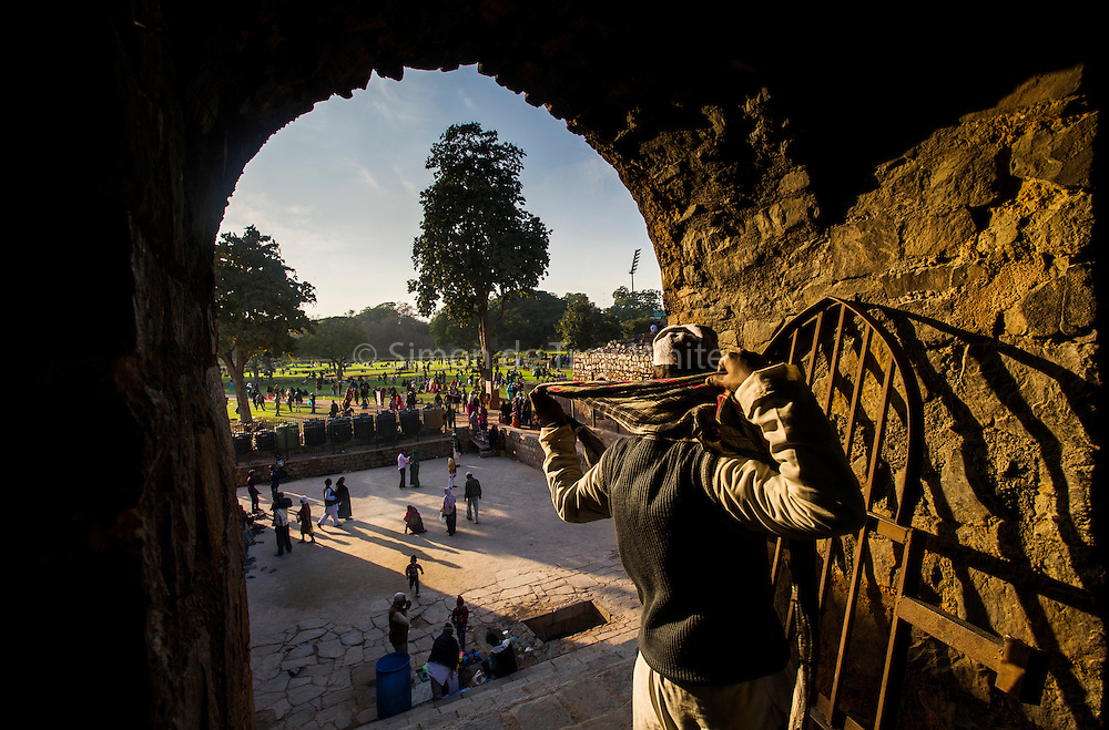 5th February 2015, New Delhi, India. A man adjusts his scarf in an arched doorway in the ruins of Feroz Shah Kotla on the 5th February 2015<br /> <br /> PHOTOGRAPH BY AND COPYRIGHT OF SIMON DE TREY-WHITE a photographer in delhi. + 91 98103 99809. Email:simon@simondetreywhite.com<br /> <br /> People have been coming to Firoz Shah Kotla to leave written notes and offerings for Djinns in the hopes of getting wishes granted since the late 1970's. Jinn, jann or djinn are supernatural creatures in Islamic mythology as well as pre-Islamic Arabian mythology. They are mentioned frequently in the Quran  and other Islamic texts and inhabit an unseen world called Djinnestan. In Islamic theology jinn are said to be creatures with free will, made from smokeless fire by Allah as humans were made of clay, among other things. According to the Quran, jinn have free will, and Iblīs abused this freedom in front of Allah by refusing to bow to Adam when Allah ordered angels and jinn to do so. For disobeying Allah, Iblīs was expelled from Paradise and called &quot;Shayṭān&quot; (Satan).They are usually invisible to humans, but humans do appear clearly to jinn, as they can possess them. Like humans, jinn will also be judged on the Day of Judgment and will be sent to Paradise or Hell according to their deeds. Feroz Shah Tughlaq (r. 1351&ndash;88), the Sultan of Delhi, established the fortified city of Ferozabad in 1354, as the new capital of the Delhi Sultanate, and included in it the site of the present Feroz Shah Kotla. Kotla literally means fortress or citadel.