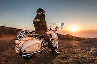Rider in black leather sitting on a 1960s BMW R60US motorcycle (PR) on the side of a coastal road in Sonoma County California, watching the sunset.