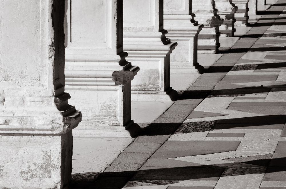 In the morning sun, the shadows of the pillars mimic the pattern on the piazza floor.