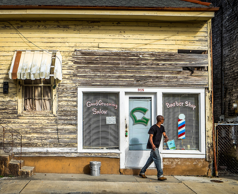 NEW ORLEANS - CIRCA FEBRUARY 2014: Man walks out of a baber shop in McDonough, a popular community within the city of New Orleans in Louisiana.
