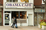 Two African-American women strolll by the Obama Cafe on Toronto's Danforth Street.