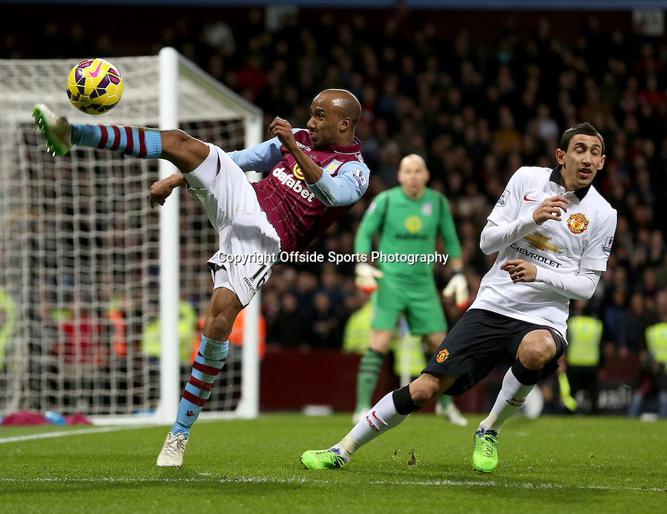20th December 2014 - Barclays Premier League - Aston Villa v Manchester United - Fabian Delph of Aston Villa clears his lines under pressure from Angel DiMaria of Manchester United - Photo: Paul Roberts / Offside.