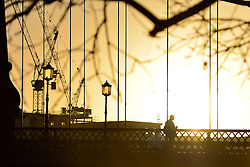 © Licensed to London News Pictures. 26/02/2014. London, UK. A commuter walks over Hammersmith Bridge. Sunrise over the River Thames at Hammersmith in West London today 26th February 2014. Photo credit : Stephen Simpson/LNP