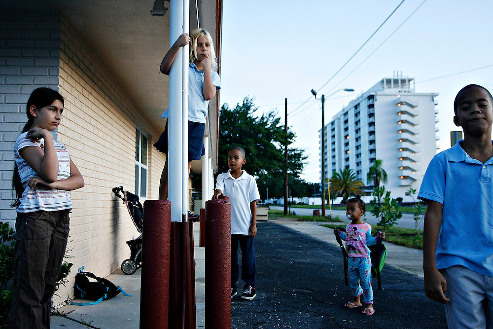MELISSA LYTTLE   |   Times<br /> SP_345156_LYTT_MOTEL_6 (November 22, 2011, St. Petersburg, FL) Valerie Drinkwater, 6, second from left, stands up on a post while waiting for the school bus with other kids from the Mosley Motel. On any given day in October about half a dozen different school buses were picking up and dropping off about 22 kids from the motel.  [MELISSA LYTTLE, Times]