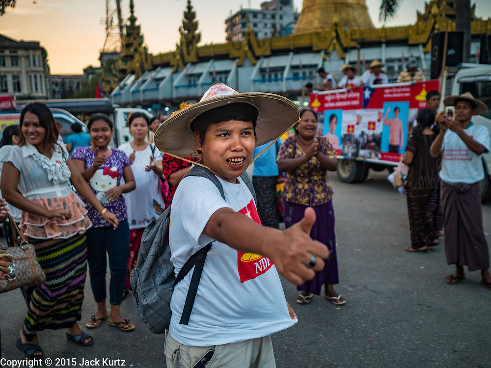06 NOVEMBER 2015 - YANGON, MYANMAR:  NDF supporters cheer at the final NDF election rally of the 2015 election. The rally was held in central Yangon, next to the historic Sule Pagoda and across the street from Yangon city hall. The National Democratic Force (NDF) was formed by former members of the National League for Democracy (NLD) who chose to contest the 2010 general election in Myanmar because the NLD boycotted that election. There have been mass defections from the NFD this year because many of the people who joined the NFD in 2010 have gone back to the NLD, which is contesting this year's election and widely expected to win it. Campaigning in the Myanmar election ended Friday. People go to the polls Sunday.    PHOTO BY JACK KURTZ