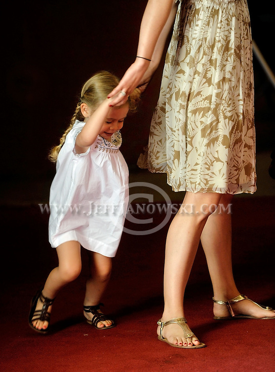 A little girl swings while holding onto her mother's hands enjoying a brief moment in her own world.