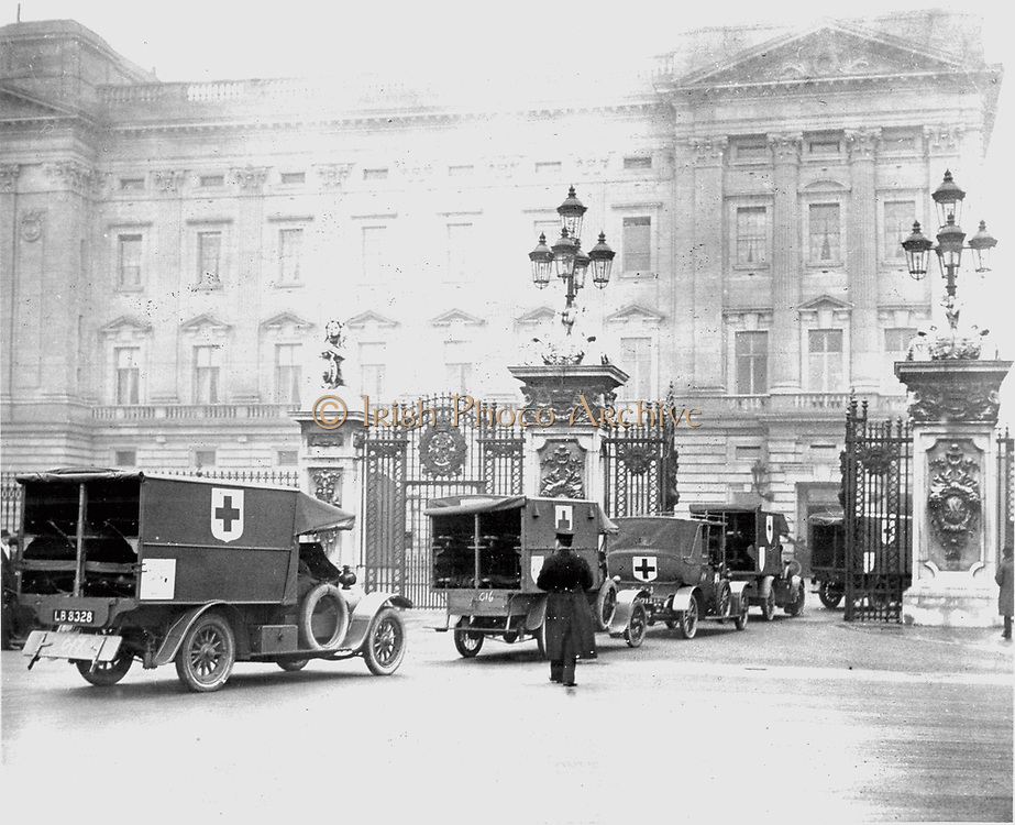 Convoy of motorised ambulances organised by the British Red Cross arriving at Buckingham Palace, London, to be reviewed by the King George V. Photograph.