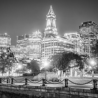 Boston skyline at night in black and white with Christopher Columbus Waterfront Park, Custom House Tower clock and downtown Boston buildings.