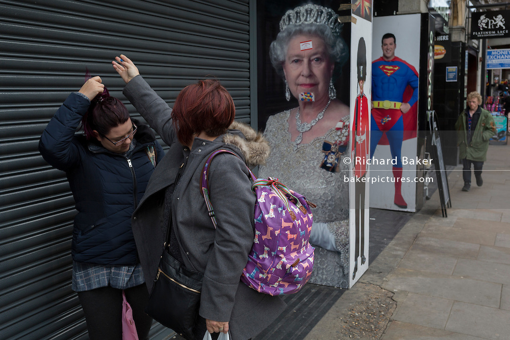 Two women fuss over hair near the images of Queen Elizabeth II, a guardsman and Superman, on 3rd February 2017, in London, England.