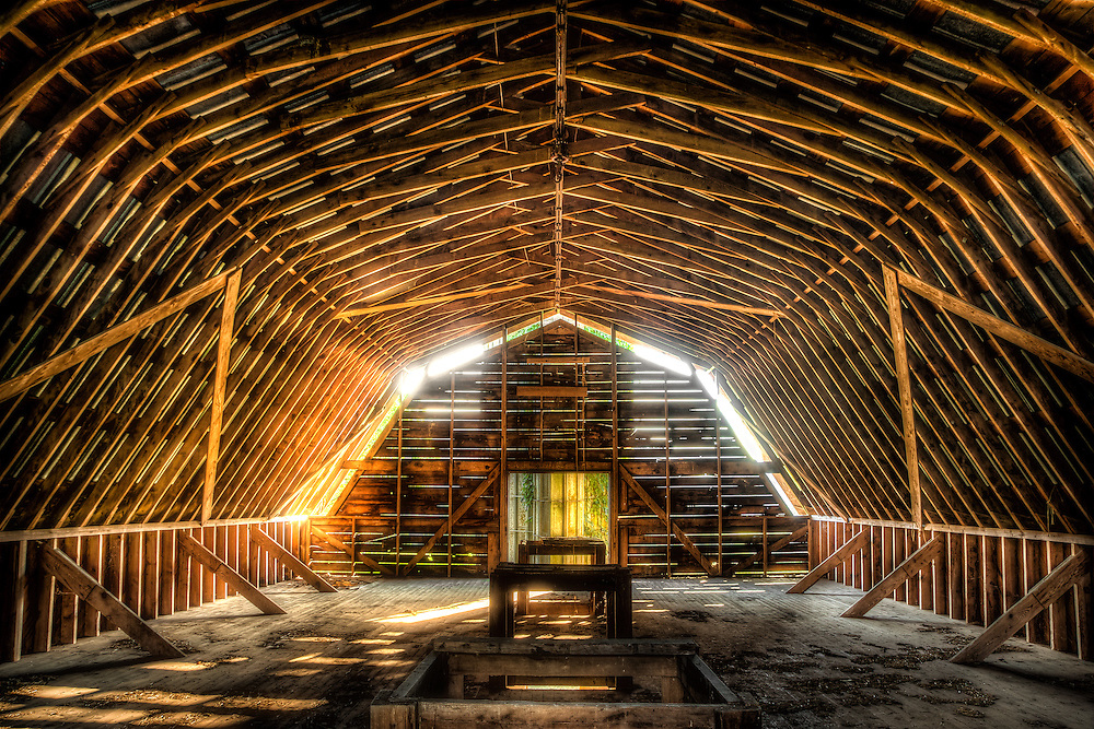 Evening sun beams shine through the crack in the boards of the loft of an old hay barn near Brevard, NC.