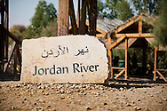 Sign for the Jordan River at Bethany-Beyond-the-Jordan, Jordan, where Jesus was baptized. The river itself is on the opposite side of the buildings in the background.