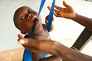 A child cries while sitting in a harness hanging from a scale at the Pujehun Government hospital in Pujehun, Sierra Leone on Friday March 19, 2010..