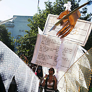 A woman in an outfit with a giant blank check and quotes from civil rights movement activists dances past the Hackney Town Hall in East London, United Kingdom,Sept 11 2016. The annual Hackney Carnival took place on a hot summers day and the procession of dancers dressed in various outfits moved through the streets to much joy of the many bystanders.
