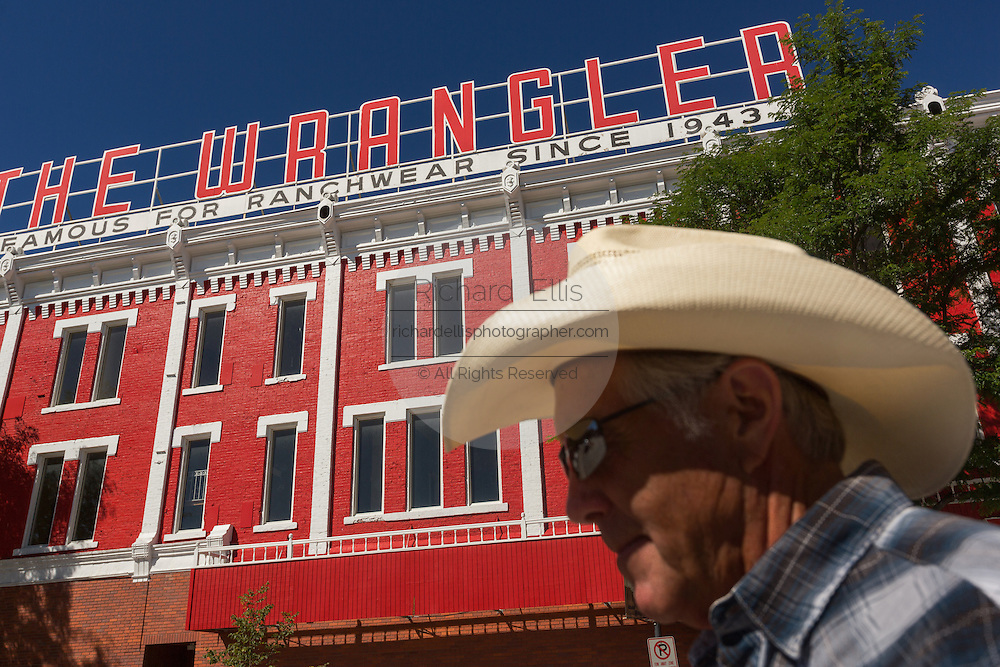A cowboy walks past the Wrangler western wear store  July 23, 2015 in Cheyenne, Wyoming. The store opened in 1943 is the largest western wear outfitter in America.