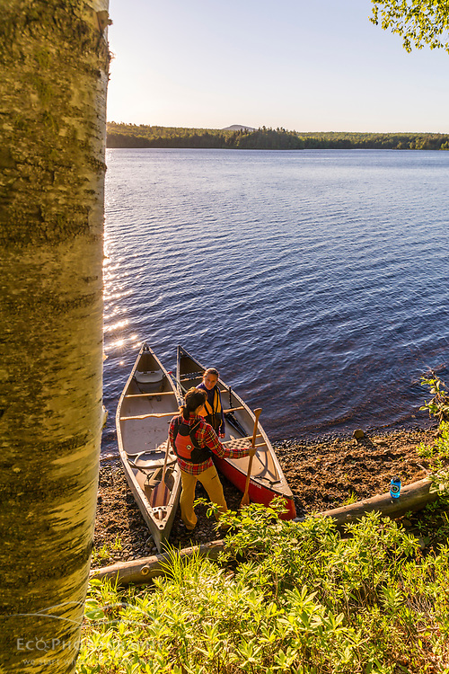 Two women take a break from paddling a canoe in the morning on Silver Lake in Piscataquis County, Maine. Near Greenville.