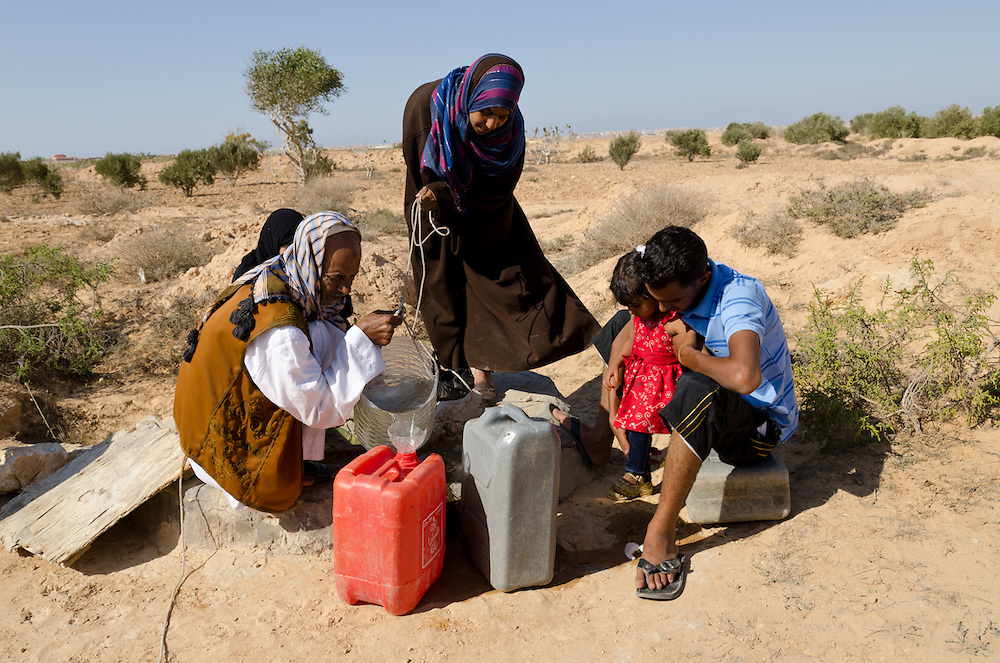 The Abdullah family takes water from a nearly empty well, near Marsa Matruh, Egypt. Eatamad, pouring water, much prefers life in the desert to life in town, but the family must live in town where there is work to be had and where children can go to school.