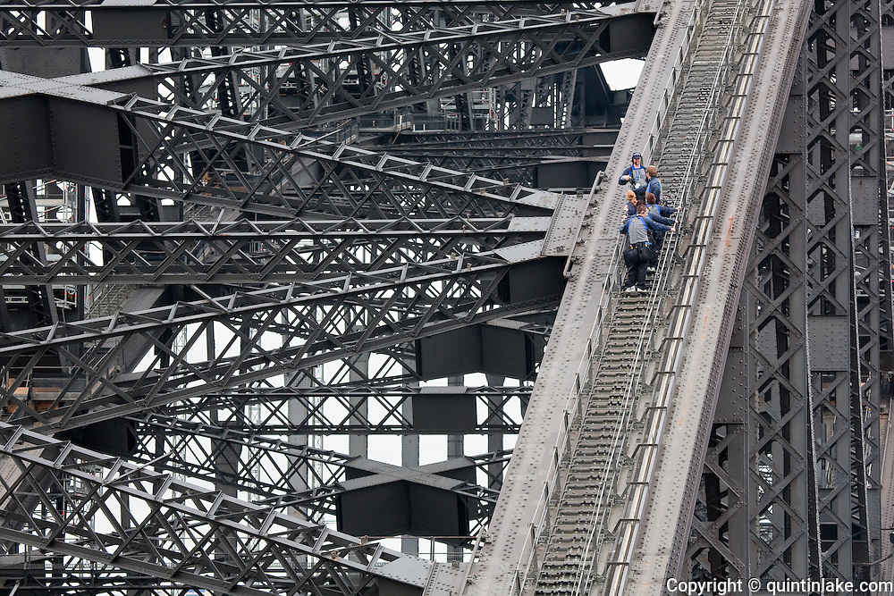 "BridgeClimb participants and guide on the Sydney Harbour Bridge, Sydney, Australia.The Sydney Harbour Bridge is a steel through arch bridge across Sydney Harbour that carries rail, vehicular and pedestrian traffic between theSydney central business district (CBD) and the North Shore. The dramatic view of the bridge, the harbour, and the nearby Sydney Opera House is an iconic image of both Sydney and Australia. The bridge is locally nicknamed ""The Coathanger"" because of its arch-based design...The bridge was designed and built by Dorman Long and Co Ltd, Middlesbrough Teesside and Cleveland Bridge, Darlington, County Durham and opened in 1932. Until 1967 it was the city's tallest structure.[citation needed] According to Guinness World Records, it is the world's widest long-span bridge and it is the tallest steel arch bridge, measuring 134 metres (440 ft) from top to water level. It is also the fifth-longest spanning-arch bridge in the world."