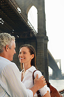 Couple embracing under Brooklyn Bridge