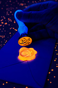 A glowing skull and crossed swords wax stamp seals an envelope. Blacklight photography.
